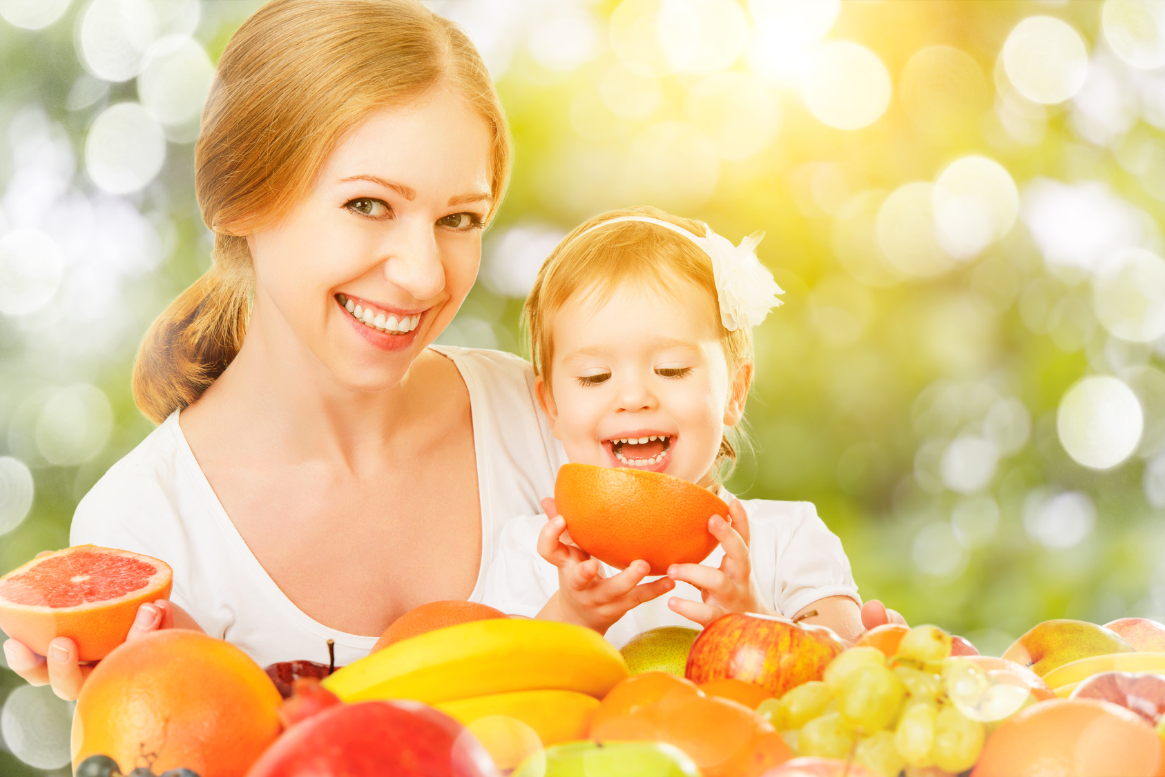 healthy vegetarian food. happy family mother and baby daughter with fruit | organic cotton baby clothes