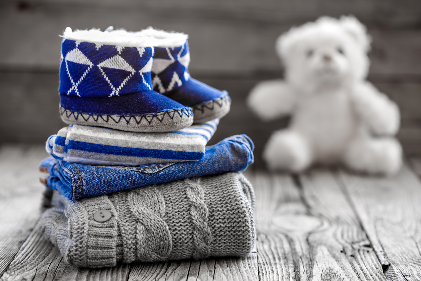 winter baby clothes in grey and blue colors piled up