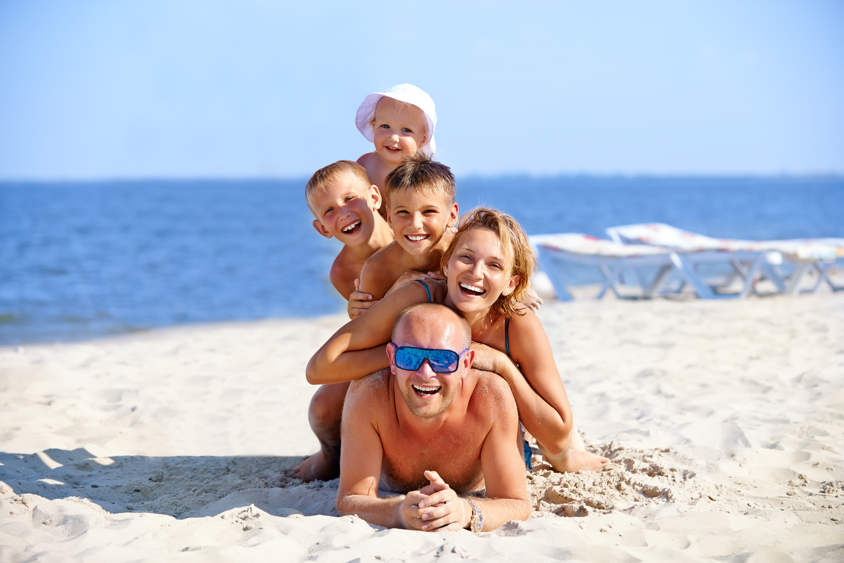 Mother and father with three children on the beach | sense organics - organic baby clothes