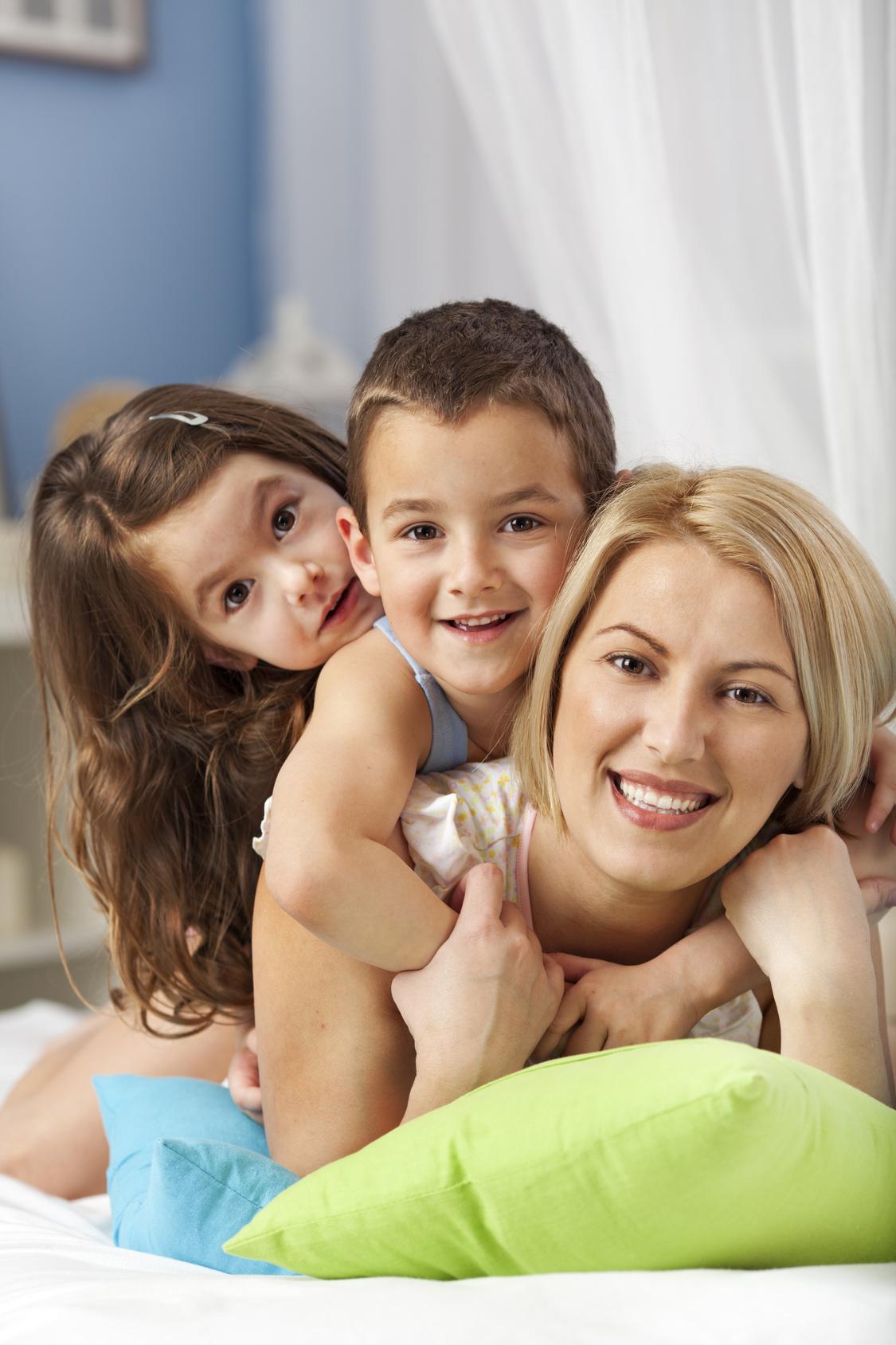 kids and mum in pajamas cuddling in bed | sense organics